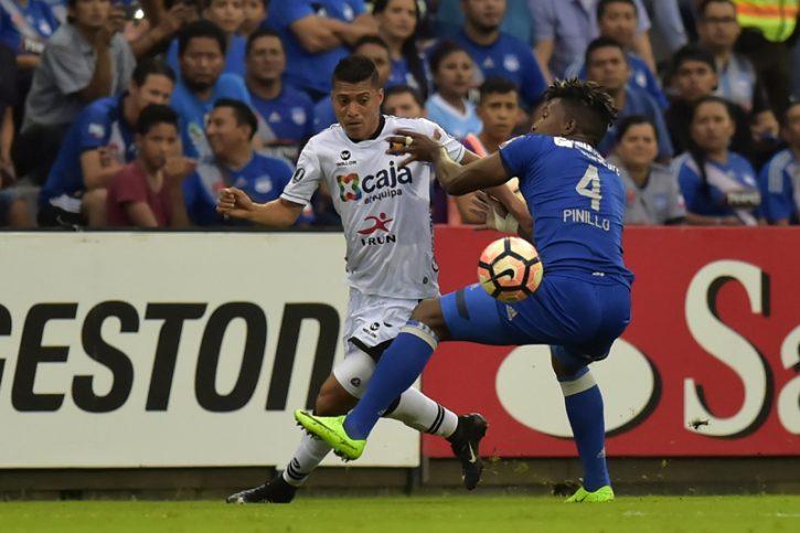 Melgar's Daniel Chavez (L) vies for the ball with Emelec's Fernando P